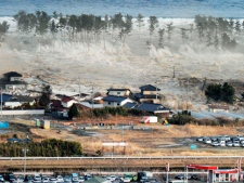 Waves of tsunami hit residences after a powerful earthquake in Natori, Japan, Friday, March 11, 2011. The largest earthquake in Japan's recorded history slammed the eastern coast Friday. (AP Photo/Kyodo News)