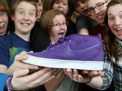 The communications club holds an autographed Justin Bieber running shoe at Bieber's former school, Northwestern Secondary School, in Stratford, Ont., Wednesday, March 9, 2011. The running shoe was auctioned on eBay as a school club fundraiser. (THE CANADIAN PRESS/Dave Chidley)