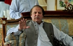 Nawaz Sharif, former prime minister and leader of the Pakistan Muslim League-N party, gestures while speaking to members of the media at his residence in Lahore, Pakistan, Monday, May 13, 2013. (AP Photo/K.M. Chaudary)