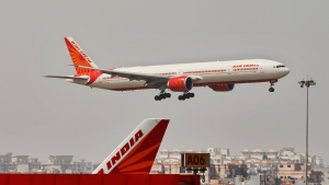 An Air India plane flies in New Delhi, India, Thursday, April 12, 2012. (AP / Tsering Topgyal)