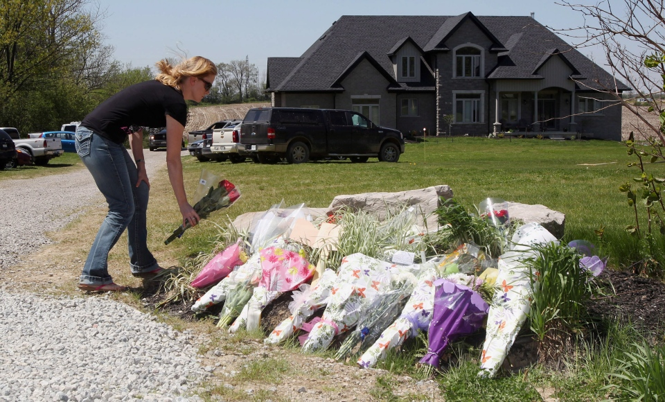 A woman places flowers in front of the Bosma family home in Ancaster on Wednesday, May 15 2013. (The Canadian Press/Dave Chidley)
