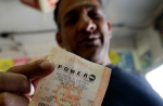 Joe Fajardo holding a Powerball lottery ticket after buying it at a store in San Diego on Saturday, May 18, 2013. (AP Photo/Gregory Bull)