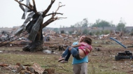 A woman carries her child through a field near the collapsed Plaza Towers Elementary School in Moore, Okla., on Monday, May 20, 2013. (AP Photo Sue Ogrocki)