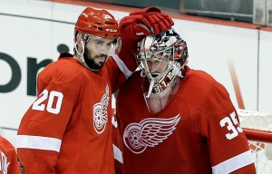 Detroit Red Wings left wing Drew Miller (20) congratulates goalie Jimmy Howard (35) after beating the Chicago Blackhawks 3-1 in a semifinal game in Detroit on Monday, May 20, 2013. (AP Photo/Paul Sancya)