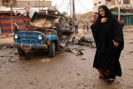 An Iraqi woman passes by the scene of a car bomb attack in Kamaliyah neighborhood, a predominantly Shiite area of eastern Baghdad, Iraq, Monday, May 20, 2013. (AP Photo/ Hadi Mizban)