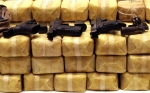 Guns are displayed on packs of confiscated methamphetamine during a police news conference at police headquarters in Bangkok, Thailand Tuesday, May 21, 2013. Police confiscated nearly 4.5 millions pills of methamphetamine and arrested three Thai people in a raid on Tuesday. (AP Photo/Apichart Weerawong)