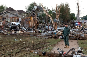 A member of a security team guards a destroyed residential neighborhood in Moore, Okla., Tuesday, May 21, 2013, one day after a tornado moved through the community. (AP Photo/Brennan Linsley)