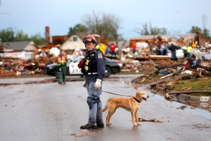 A rescuer searches a neighborhood near Telephone Road in Moore, Okla., on Tuesday, May 21, 2013. (AP Photo/The Oklahoman, Sarah Phipps)