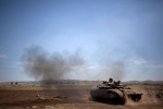 An Israeli soldier drives a tank in the Israeli-controlled Golan Heights, near the border with Syria, Wednesday, May 22, 2013. (AP Photo/Ariel Schalit)