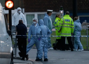 Police and forensic officers near the scene of a deadly attack near Woolwich barracks in London on Wednesday, May, 22, 2013. (AP Photo/Alastair Grant)