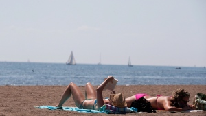 People read as they sunbathe on a warm summer day at Cherry Beach in Toronto on Thursday, Aug. 23, 2012. (The Canadian Press/Michelle Siu)