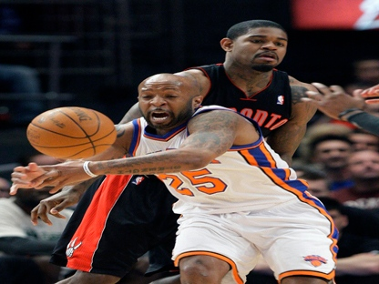 New York Knicks' Anthony Carter (25) attempts to break up a pass by Toronto Raptors' Amir Johnson, right, during the first half of an NBA basketball game Tuesday, April 5, 2011, in New York. (AP Photo/Frank Franklin II)