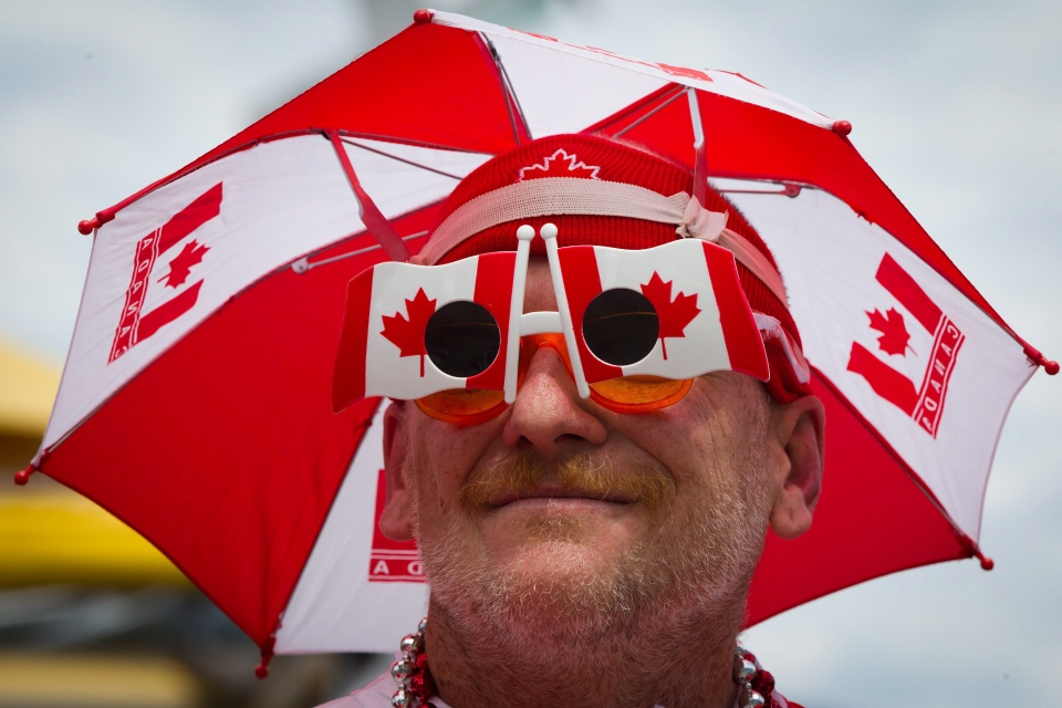Hugh McPherson wears Canadian flag glasses and an umbrella while attending Canada Day festivities in Vancouver, B.C., on Monday, July 1, 2013. (Darryl Dyck / The Canadian Press)