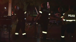 Paramedics wheel a stabbing victim to an ambulance near Lake Shore Boulevard East and Woodbine Avenue after Canada Day fireworks Monday, July 1, 2013.