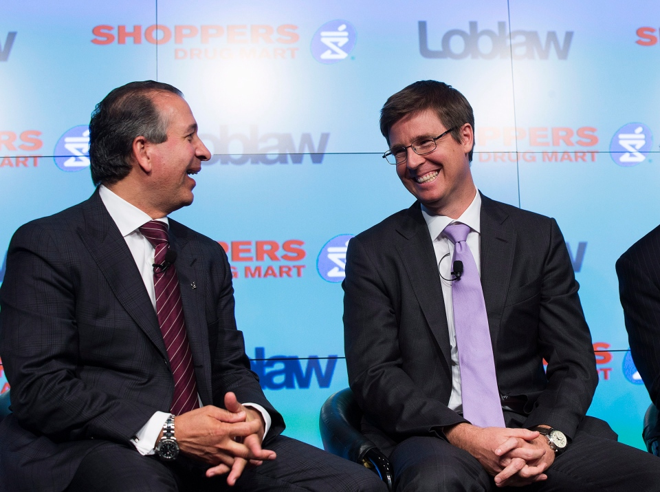 Domenic Pilla, president and CEO of Shoppers Drug Mart Corp., left, and Galen G. Weston, executive chairman of Loblaw, answer questions from the media at a press conference in Toronto on Monday, July 15, 2013. (The Canadian Press/Michelle Siu)
