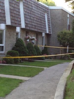 Police tape surrounds a townhouse complex Tuesday, July 16, 2013, a day after three people were found dead. (Katie Simpson/CP24)