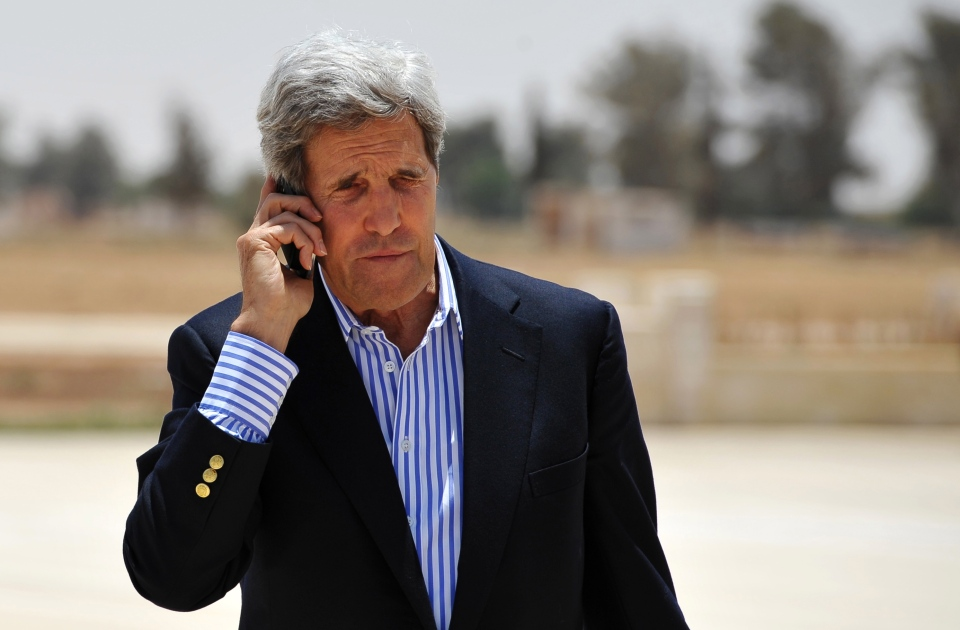 U.S. Secretary of State John Kerry speaks on the phone, before boarding a helicopter to Amman, at Mafraq air base after visiting the Zaatari refugee camp in Mafraq, Jordan, on Thursday, July 18, 2013. (AP /Mandel Ngan)