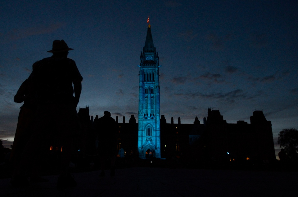 The Peace Tower and Parliament buildings are illuminated in royal blue to celebrate the birth of a royal baby on Monday, July 22, 2013 in Ottawa. (The Canadian Press/Adrian Wyld)