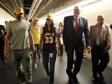 Los Angeles Lakers coach Phil Jackson, second from right, walks down a tunnel with members of his family after the Dallas Mavericks' 122-86 win in Game 4 of a second-round NBA playoff basketball series, Sunday, May 8, 2011, in Dallas. The Mavericks swept the series. (AP Photo/Tony Gutierrez)