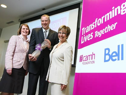 Darrell Gregersen, left, President and CEO of the Centre for Addiction and Mental Health Foundation, and Dr. Catherine Zahn, right, President and CEO of CAMH, present George Cope, President and CEO of Bell and BCE Inc., with a hand-blown hourglass containing crushed brick from a torn-down CAMH building, Wednesday, May 11, 2011, in Toronto. Bell's $10 million gift is the largest corporate donation to mental health in Canada, bringing CAMH's Transforming Lives Campaign to a historic high of $108 million. (The Canadian Press Images PHOTO/CAMH Foundation)