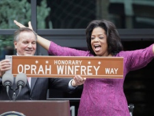 In one of his last acts before leaving office next week, Chicago Mayor Richard M. Daley presents TV talk-show host Oprah Winfrey with a sign after a street was named in her honor outside her Harpo Studios in Chicago, Wednesday, May 11, 2011. Winfrey will end her 25 year-run on daytime television in Chicago on May 25. (AP Photo/M. Spencer Green)