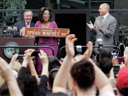In this photo taken May 11, 2011, fans applaud as talk-show host Oprah Winfrey is honored with a street named for her outside her Harpo Studios in Chicago by Chicago Mayor Richard M. Daley, left, and Bobby Ware, commissioner of the Chicago Department of Transportation. Winfrey's talk show, which has taped in Chicago for 25 years, ends May 25, 2011. (AP Photo/M. Spencer Green)