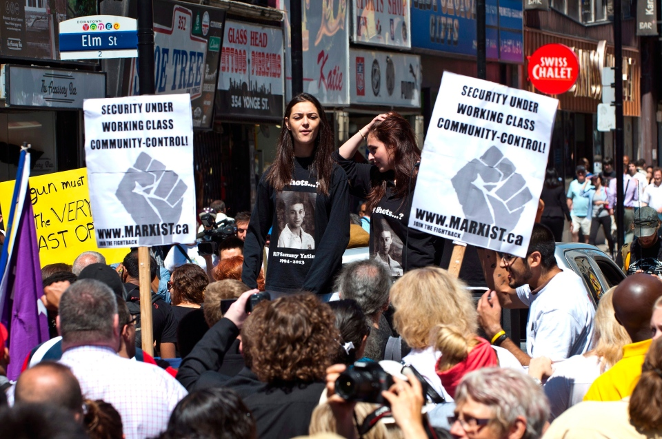 Sarah Yatim, right, and friends lead protesters in a march to Toronto Police headquarters to protest the fatal shooting of her brother, Sammy Yatim, by police during a public protest in Toronto on Wednesday, August 13, 2013. THE CANADIAN PRESS/Galit Rodan