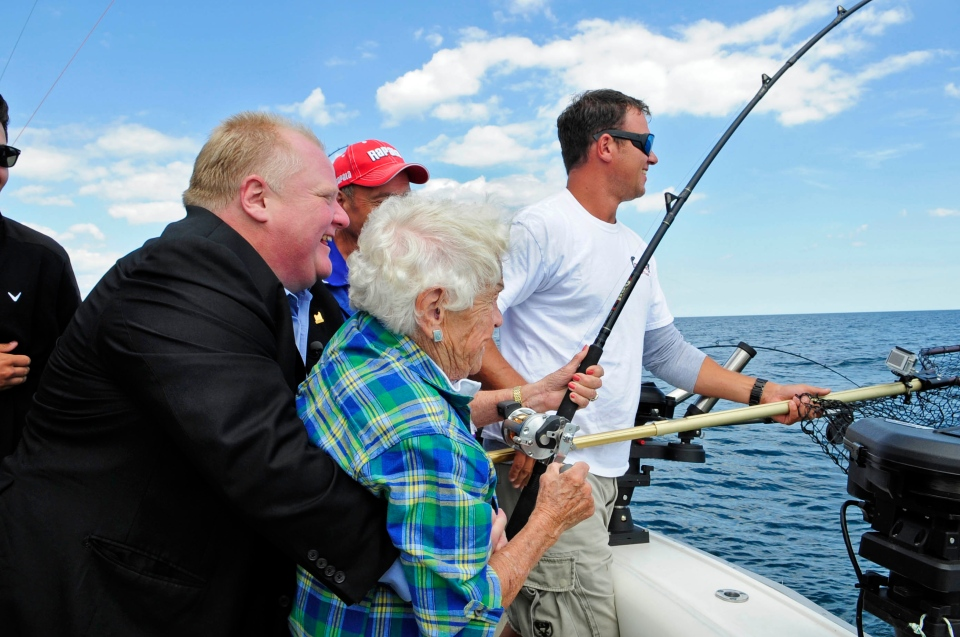 Toronto Mayor Rob Ford wraps his arms around Mississauga Mayor Hazel McCallion as she reels in a salmon on Lake Ontario on Thursday, Aug. 15, 2013. (Photo courtesy of Canadian Sportfishing)