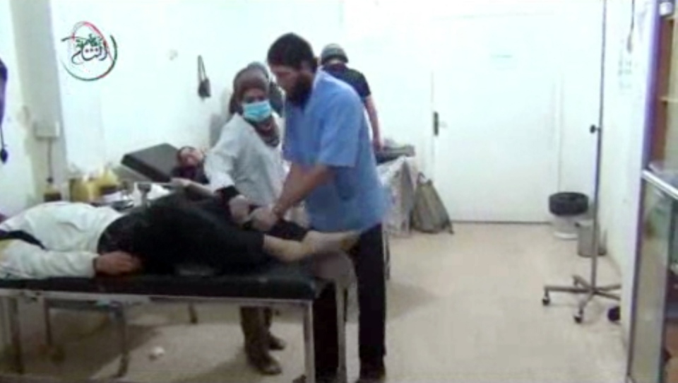 This Monday, Aug. 26, 2013, image taken from amateur video footage provided by the Media Office Of Moadamiyeh purports to show medics assisting a man lying on a bed who appears to be shaking uncontrollably as a UN inspection team visits a makeshift hospital in Moadamiyeh, a suburb of the Syrian capital of Damascus. (AP Photo/Media Office Of Moadamiyeh)
