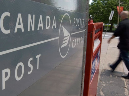 A man walks past Canada Post mail boxes in Ottawa, Monday May 30, 2011. (THE CANADIAN PRESS/Adrian Wyld)