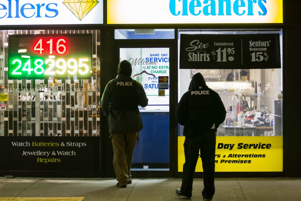 Police officers enter Richview Cleaners in Etobicoke during a search early Wednesday, Oct. 2, 2013. (Tom Stefanac/CP24)