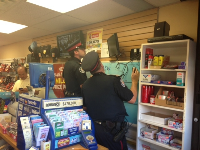 Police officers examine surveillance video at a store in Richview Square after police charged Alexander (Alessandro) Lisi with drug-related offences Wednesday, Oct. 2, 2013. (Cam Woolley/CP24)