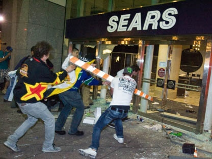 Rioters break the front doors of a Sears department store on Granville Street during the riot following Game 7 of the NHL Stanley Cup final in downtown Vancouver, B.C., on Wednesday, June 15, 2011. (THE CANADIAN PRESS/Geoff Howe)