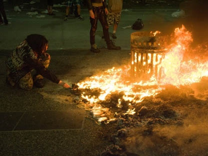 A woman lights her cigerette from a fire during a riot following Game 7 of the NHL Stanley Cup final in downtown Vancouver, B.C., on Wednesday, June 15, 2011. (THE CANADIAN PRESS/Geoff Howe)