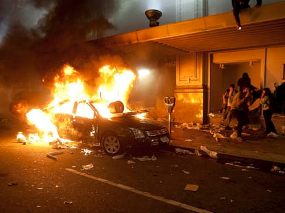 A car burns outside The Bay department store during a riot in downtown Vancouver, B.C., Wednesday, June 15, 2011 following the Vancouver Canucks' 4-0 loss to the Boston Bruins in Game 7 of the Stanley Cup hockey final. (THE CANADIAN PRESS/Ryan Remiorz)