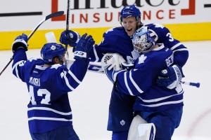 Toronto Maple Leafs players Jonathan Bernier, right, Carl Gunnarsson, centre, and Nazem Kadri celebrate a win over the Ottawa Senators in a shootout in Toronto on Saturday, Oct. 5, 2013. (The Canadian Press/Mark Blinch)