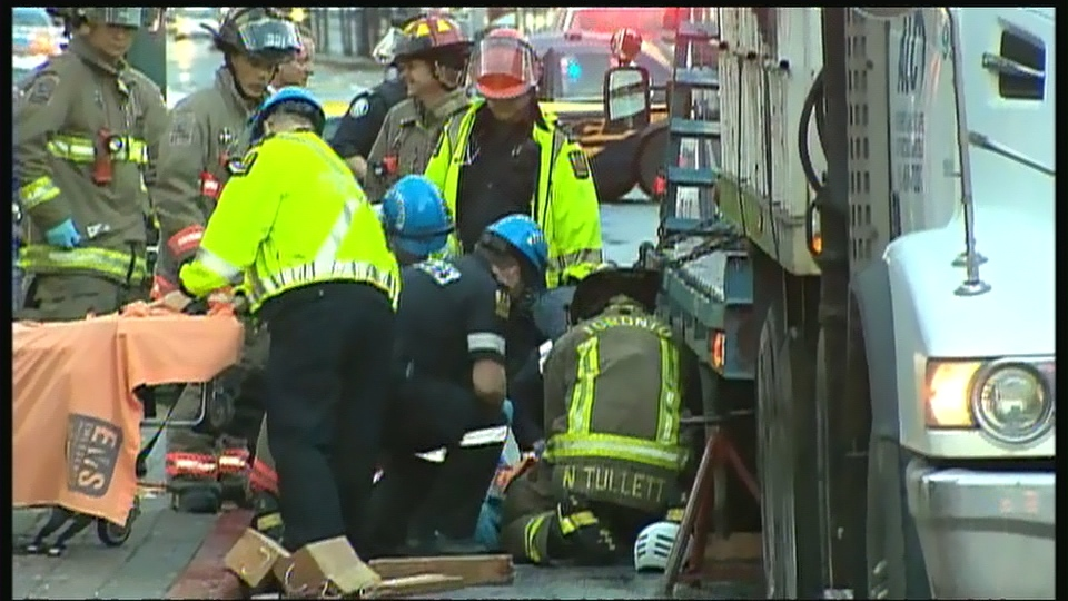 Firefighters and paramedics work to free a female cyclist after she was struck by a large truck on Spadina Avenue, near Dundas Street West, on Wednesday, Oct. 16, 2013.