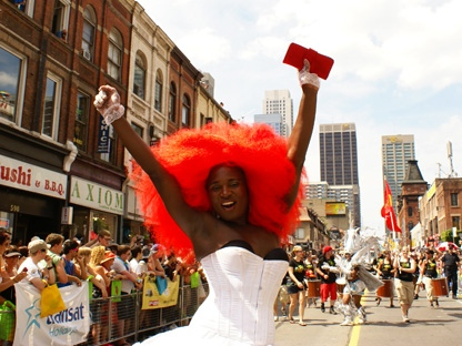 A participant in Toronto's annual Pride parade celebrates as the parade makes its way south on Yonge Street. Some estimates pegged the crowd at one million. More than 6,000 people marched or rode on floats. (CP24/Chris Kitching)