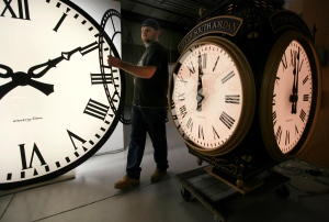 In this Thursday, Nov. 3, 2011 photo, Dan LaMoore of Electric Time Company moves a clock face at their plant in Medfield, Mass., between a large tower clock, left, bound for King of Prussia, Pa., and a post clock headed to South Jordan, Utah, right.  (AP /Elise Amendola)