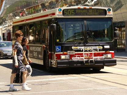 People cross the street in front of a TTC bus in this Thursday, June 30, 2011 file photo. (CP24/Chris Kitching)