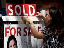"""A real estate agent puts up a """"sold"""" sign in front of a house in Toronto on Tuesday, April 20, 2010. The Canadian Real Estate Association says Canada's home prices continued to rise last month and a majority of the country's local markets showed a balance between supply and demand, including in Toronto. (THE CANADIAN PRESS/Darren Calabrese)"""