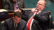 Toronto Mayor Rob Ford makes a drinking and driving gesture to Coun. Paul Ainslie in the council chamber as councillors consider a motion to limit the mayor's powers Monday, Nov. 18, 2013. (The Canadian Press/Chris Young)