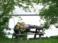 A man takes to the shade and has a nap at Sunnyside Beach on Lake Ontario in Toronto on Wednesday, June 8, 2011. (THE CANADIAN PRESS/Nathan Denette)
