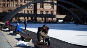 A couple enjoy a moment as they sit on the edge of the skating rink in Toronto's Nathan Phillips square on Tuesday, March 5, 2013. (The Canadian Press/Chris Young)