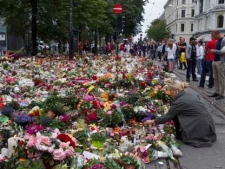 A woman places flowers amongst candles and other floral tributes in Oslo, Norway on Monday July 25, 2011 in memory of the victims of Friday's bomb blast and shooting massacre. (AP Photo/Scanpix Norway/Berit Roald/Scanpix Norway)
