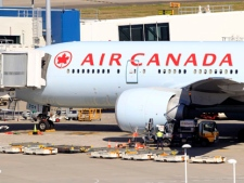 An Air Canada Boeing 777 sits at a gate after it was forced to return to Sydney Airport in Sydney, Thursday, July 28, 2011, after crew members saw smoke coming from an oven in the galley. No one on Flight AC34 was injured in the incident, which forced the pilot to dump fuel before safely landing. (AP Photo/Rick Rycroft)