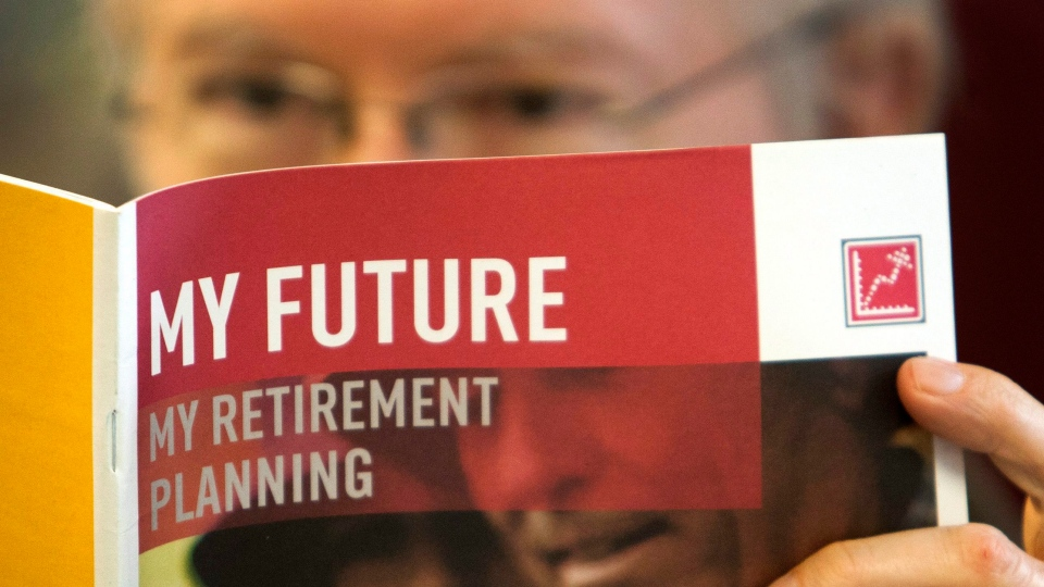 A man looks over a brochure offering retirement savings options. (The Canadian Press/Ryan Remiorz)