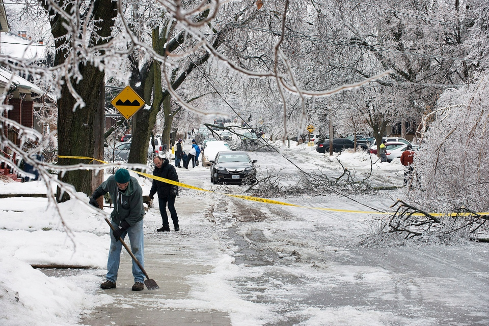 Pedestrians clear the sidewalks on a closed off Soudan Ave. in Toronto after an ice storm caused havoc knocking down trees and power lines in much of the city on Sunday, December 22, 2013. (Aaron Vincent Elkaim/The Canadian Press)