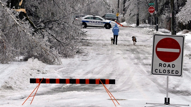 A pedestrian walks down a street still closed due to downed power lines and trees in Brampton, Ont., Monday, December 23, 2013. Hydro companies in the Greater Toronto Area — which appeared to be the hardest hit by the weather system — warned some residents to brace for the possibility of being without power until Boxing Day or later. THE CANADIAN PRESS/J.P. Moczulski