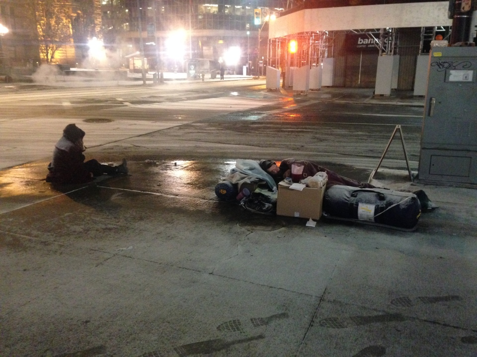 A homeless man sleeps on the sidewalk at Bay and Queen streets while another sits nearby during an extreme cold weather alert in Toronto early Thursday, Jan. 2, 2014. (Chris Kitching/CP24)